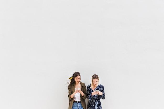 Deux jeunes femmes à l'aide de téléphones portables sur fond blanc