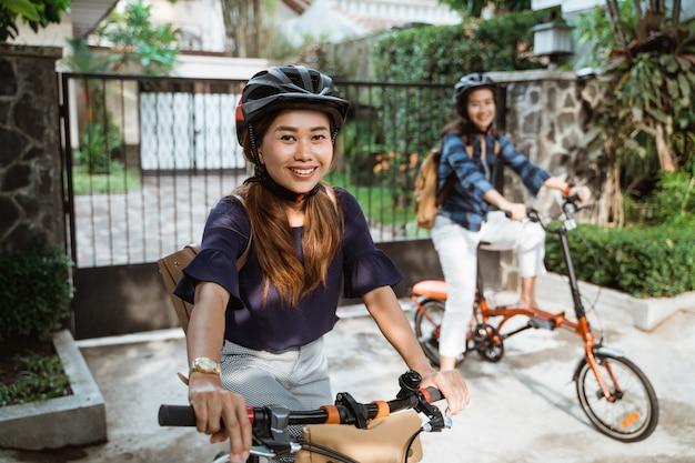 Deux jeunes femmes asiatiques portant casque et sacs prêts aller sur le campus