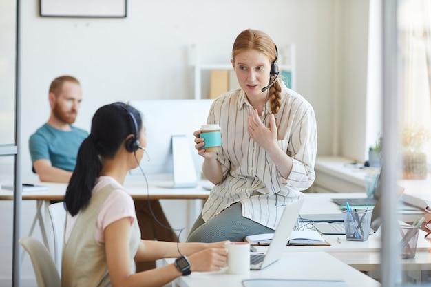 Deux jeunes femmes au casque buvant du café et se parlant pendant la pause-café au bureau