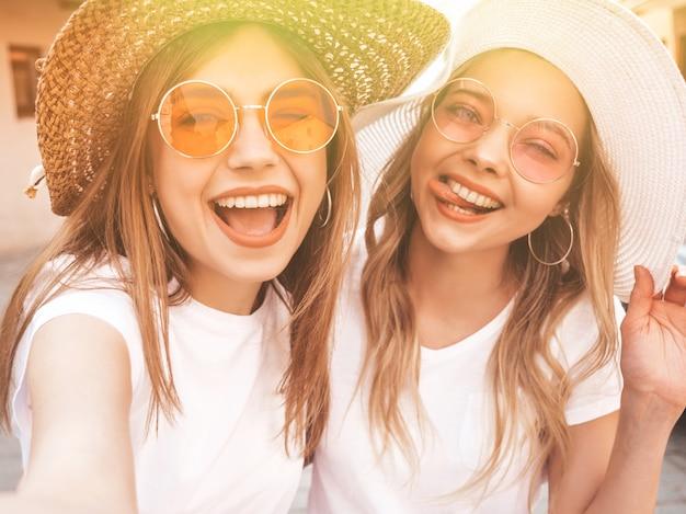 Deux jeunes femmes blondes hipster souriant dans des vêtements de t-shirt blanc d'été. filles prenant des photos d'autoportrait selfie sur smartphone.