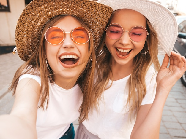Deux jeunes femmes blondes hipster souriantes en t-shirt blanc d'été. filles, prendre, selfie, autoportrait, photos, sur, smartphone., modèles, poser, sur, rue, arrière-plan., femme, montre, langue, et, émotions positives