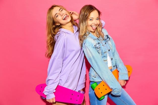 Deux jeunes femmes blondes souriantes élégantes avec des planches à roulettes penny. femmes en vêtements de sport hipster d'été posant près du mur rose. modèles positifs montrant leur langue