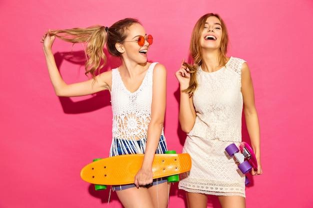 Deux jeunes femmes blondes souriantes élégantes avec des planches à roulettes penny. modèles en vêtements blancs d'été hipster posant près du mur rose en lunettes de soleil. femme positive