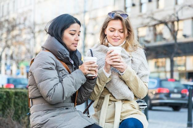 Deux jeunes femmes avec boisson chaude