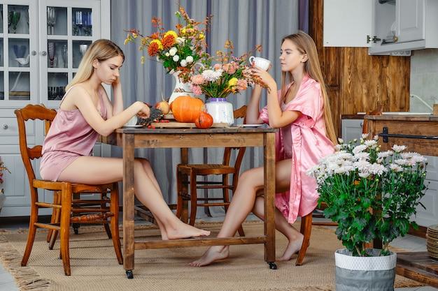 Deux jeunes femmes buvant du thé dans une cuisine rustique et parlant