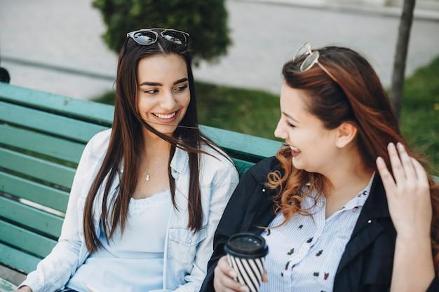 Deux jeunes femmes caucasiennes parlant souriant alors qu'il était assis sur un banc à l'extérieur de boire du café.