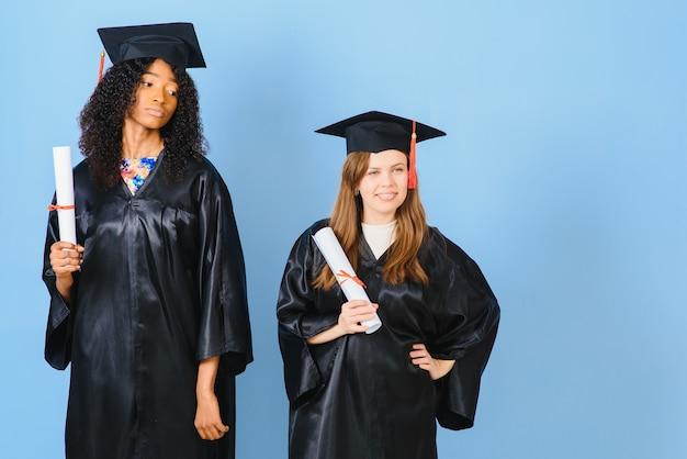 Deux jeunes femmes célébrant leur diplôme avec des diplômes