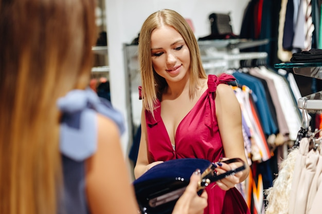 Deux jeunes femmes choisissant un sac dans une salle d'exposition