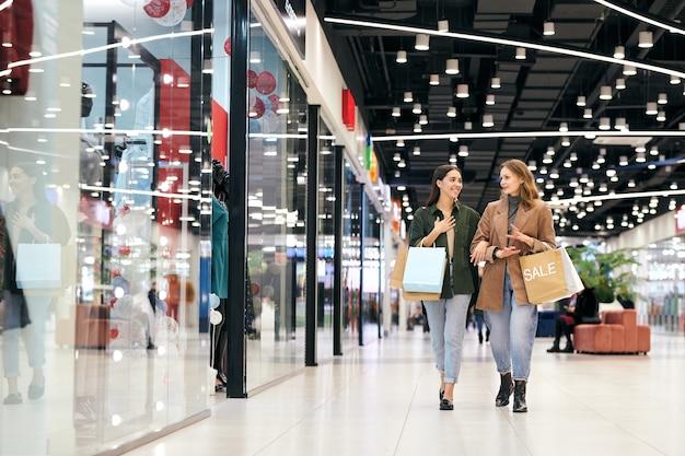 Deux jeunes femmes contemporaines en vêtements décontractés élégants marchant le long des vitrines à l'intérieur du centre commercial et discutant de ce qu'elles aimeraient acheter