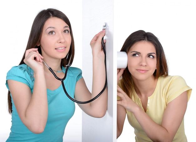 Deux jeunes femmes curieuses écoutant à travers le mur.