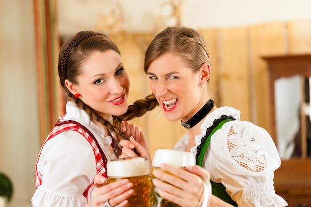 Deux jeunes femmes dans un tracht bavarois traditionnel au restaurant ou au pub