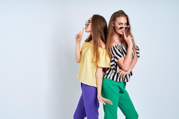 Deux jeunes femmes dans des vêtements élégants fashion studio de beauté tourné sur fond blanc