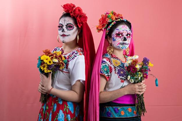 Deux jeunes femmes déguisées en catrinas avec des costumes mexicains, posant avec un fond uni et des fleurs