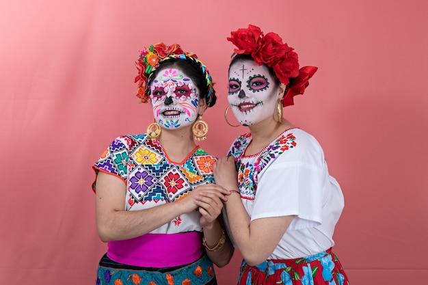 Deux jeunes femmes déguisées en catrinas avec des costumes mexicains, posant avec un fond uni