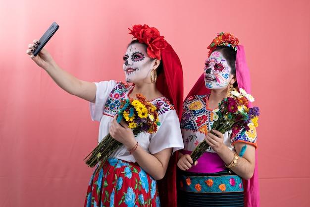 Deux jeunes femmes déguisées en catrinas avec des costumes mexicains, prenant un selfie avec des fleurs