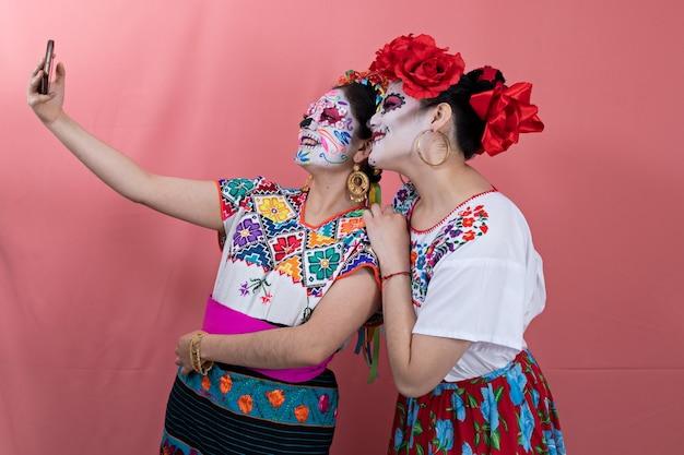 Deux jeunes femmes déguisées en catrinas avec des costumes mexicains et prenant un selfie