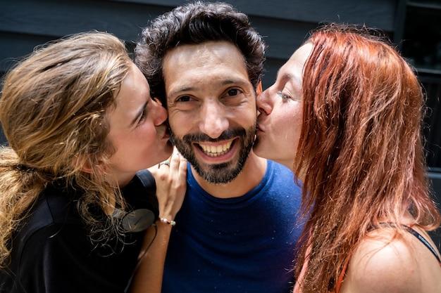 Deux jeunes femmes donnant un baiser sur chaque joue à un jeune homme d'origine ethnique différente avec une barbe et une moustache dans la rue
