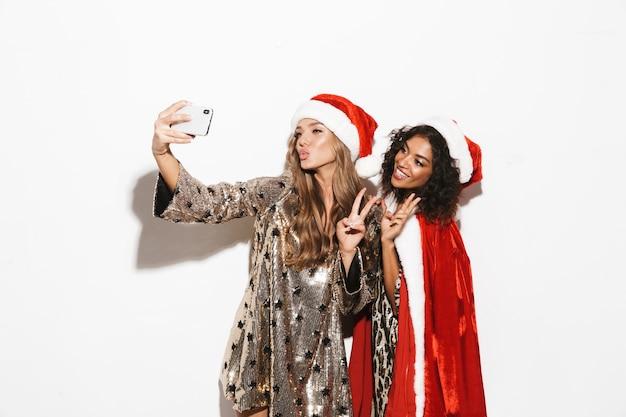 Deux jeunes femmes élégamment habillées joyeuses célébrant le nouvel an isolé sur l'espace blanc