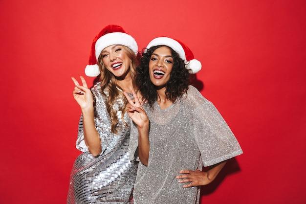 Deux jeunes femmes élégamment habillées joyeuses célébrant le nouvel an isolé sur un espace rouge