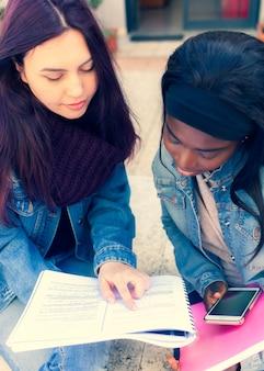 Deux jeunes femmes étudient sur un banc.