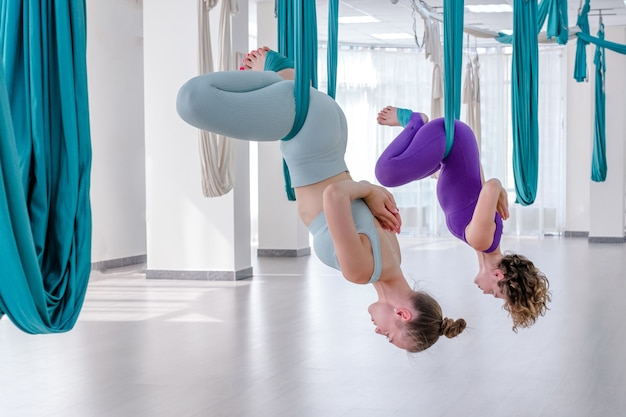 Deux jeunes femmes faisant une pose de papillon dans le yoga aérien