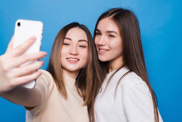 Deux jeunes femmes faisant selfie photo sur mur bleu