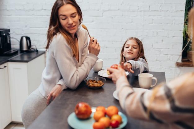 Deux jeunes femmes et une fille dans la cuisine dînent ensemble.