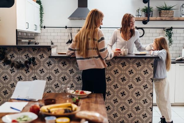 Deux jeunes femmes et une fille en train de dîner ensemble