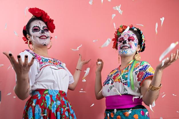 Deux jeunes femmes habillées en catrinas en costumes mexicains, posant avec un fond uni et des pétales de fleurs