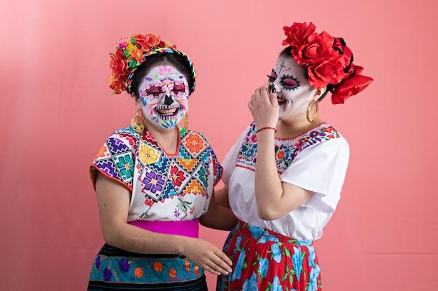 Deux jeunes femmes habillées en catrinas avec des costumes mexicains, posant avec un fond uni et riant