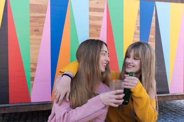 Deux jeunes femmes heureux toast avec boisson avec un multicolore