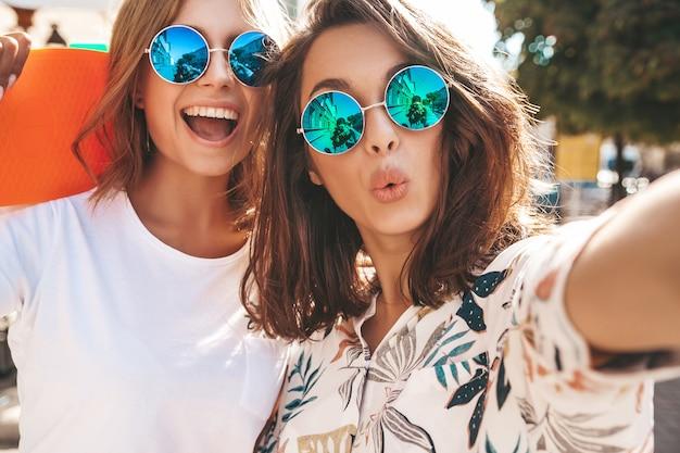 Deux jeunes femmes hippie élégante brune et blonde femmes en vêtements d'été hipster prenant selfie