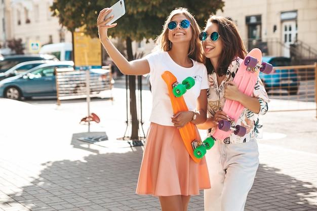 Deux jeunes femmes hippies élégantes brune et blonde. modèles en journée ensoleillée d'été dans des vêtements hipster prenant des photos de selfie pour les médias sociaux sur le téléphone. avec penn coloré