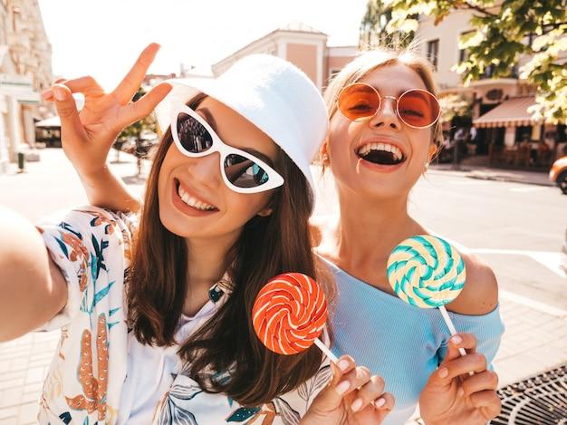 Deux jeunes femmes hipster souriantes dans des vêtements d'été décontractés.