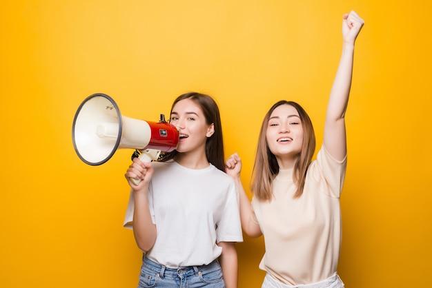 Deux jeunes femmes irritées amis filles crient dans un mégaphone isolé sur un mur jaune. concept de mode de vie des gens. maquette de l'espace de copie.