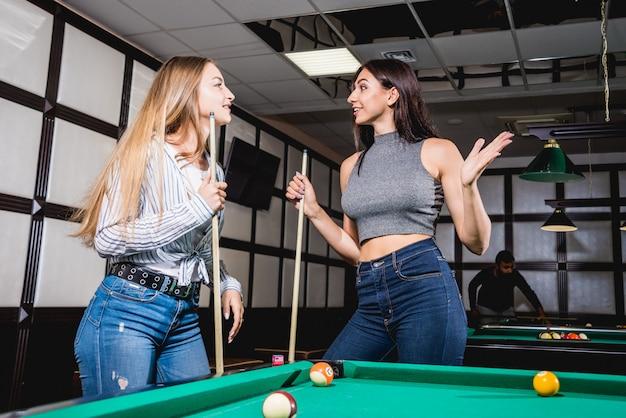 Deux jeunes femmes jouant au billard.