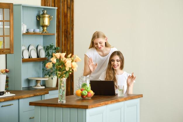 Deux jeunes femmes joyeuses faisant un appel vidéo en ligne sur ordinateur portable, renonçant à la main et en riant