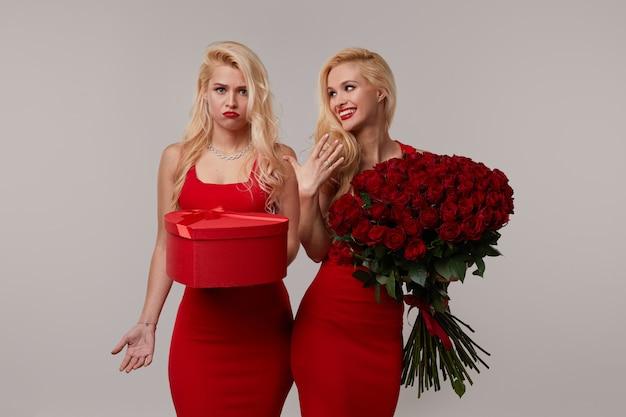 Deux jeunes femmes jumelles heureux avec un gros bouquet de roses rouges et une boîte en forme de coeur rouge.