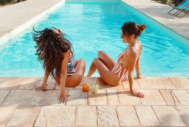 Deux jeunes femmes en maillot de bain se détendre et boire des cocktails tropicaux dans la piscine se bouchent