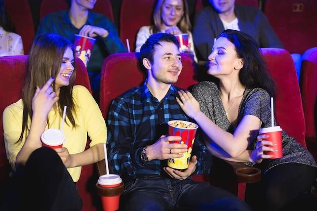 Deux jeunes femmes et un mec regardant une comédie dans un cinéma