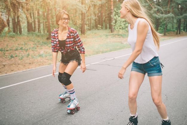 Deux jeunes femmes minces et sexy et patins à roulettes. une femelle a des patins à roues alignées et l'autre a des patins à quatre roues. les filles montent dans les rayons du soleil