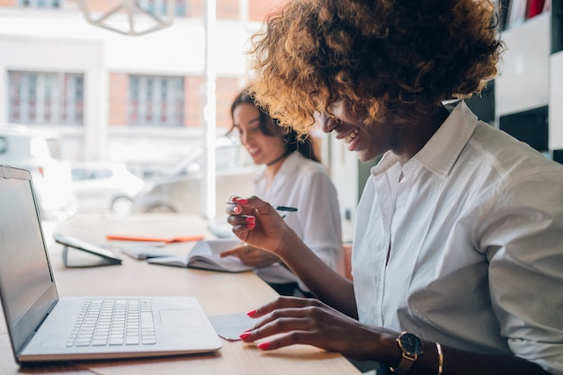 Deux jeunes femmes multiraciales écrivant et travaillant ensemble sur un projet
