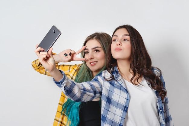 Deux jeunes femmes prenant selfie avec téléphone portable sur blanc