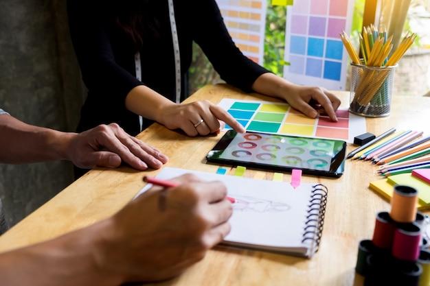 Deux jeunes femmes qui travaillent comme créateurs de mode et dessinent des croquis et obtiennent des conseils en tissu sur un tailleur personnalisé
