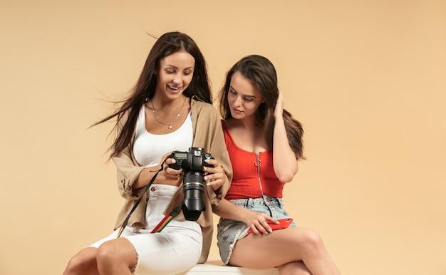 Deux jeunes femmes regardant des photos sur un appareil photo professionnel sur fond beige