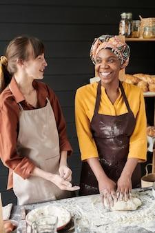 Deux jeunes femmes riant et parlant en cuisinant ensemble dans la cuisine