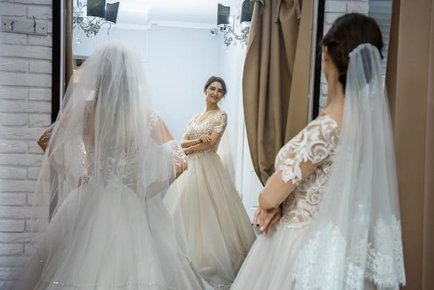 Deux jeunes femmes en robes de mariée posant devant miroir