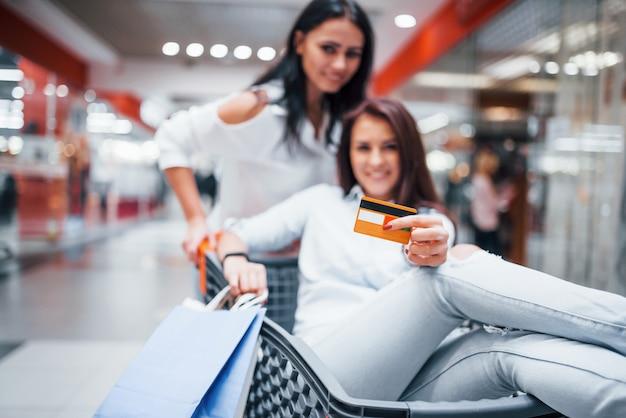 Deux jeunes femmes s'amusent en courant et en roulant dans le panier du supermarché.