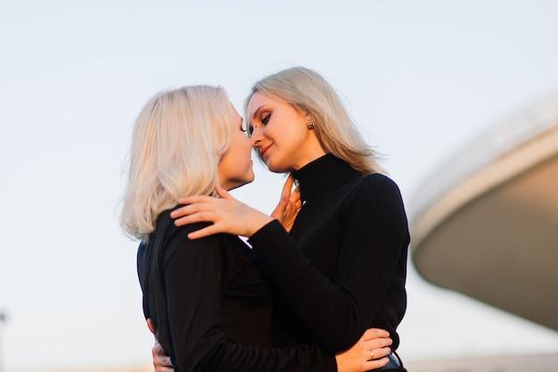 Deux jeunes femmes s'embrassant en plein air dans la ville
