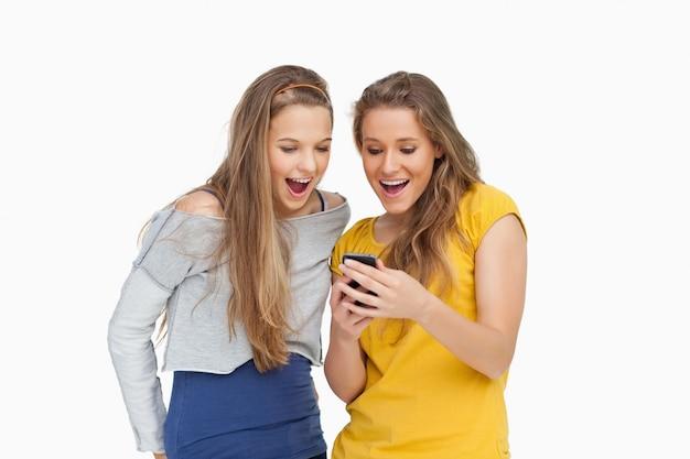 Deux jeunes femmes sans voix à la recherche d'un smartphone sur fond blanc
